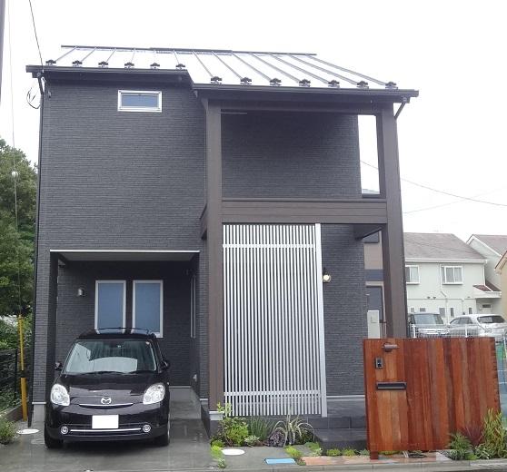 黒と木目でシックな色合い。格子の向こうにはスライド型の玄関ドアです。
