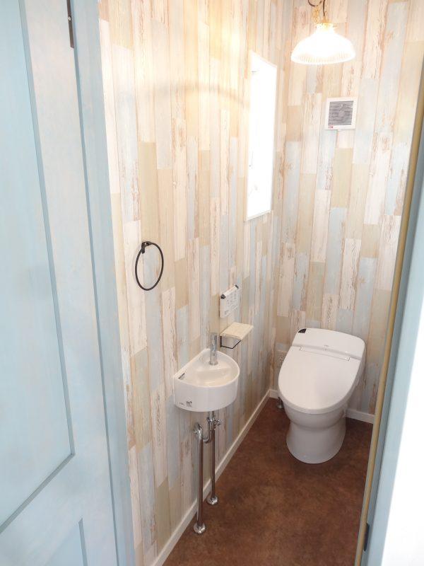 お店のトイレのようです。壁、床はもちろん、照明や小物が効いています。