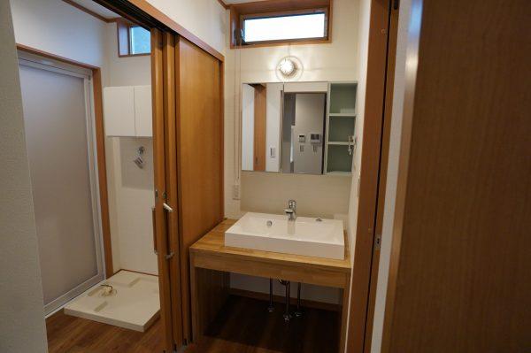 造作の洗面台は照明が印象的です。脱衣室を分けました。広く開ける3連引き戸を採用しています。