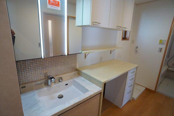 洗面室も広々サイズ。家事や収納に便利なカウンターと戸棚・引き出しをオーダーで作りました。