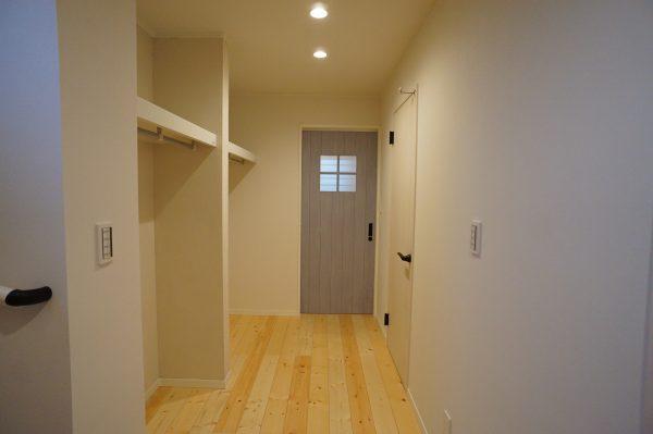 この収納壁も珪藻土、奥に見えるドアはデ玄関から入るを正面に見えるのでここだけデザインを変えています