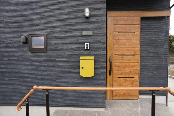 差し色のポストが映えますね。照明・表札とのバランスも良いです。玄関ドアは引き戸を採用しました。