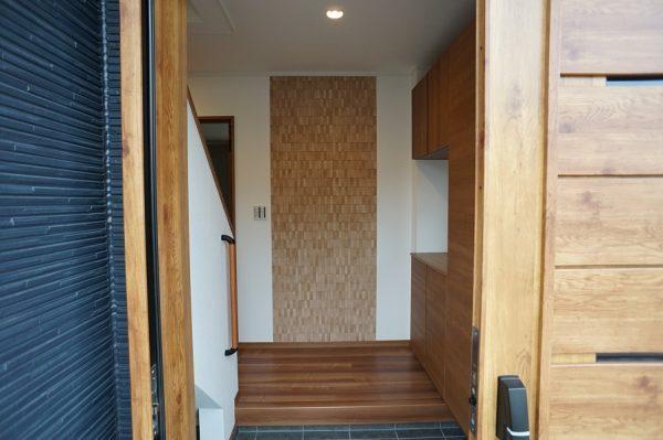 今回、3ヶ所リクシルの『エコカラット』を設置しました。  部屋の中の湿気やニオイ、有害物質を吸収してくれる壁材で、デザインも豊富にある人気の製品です。  まず、玄関の正面には『ラフソーン』という木材を粗く切ったようなレリーフです。