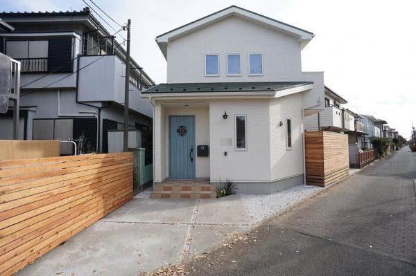 グリーンの屋根とブルーの玄関にウッドフェンスがバランス良い配色になっています。玄関前とウッドデッキの向こうで2台駐車可能です。